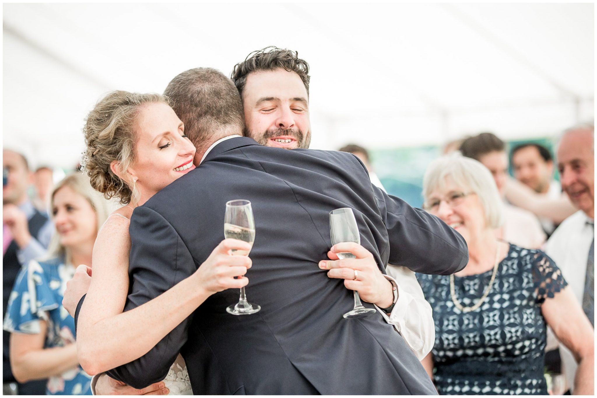 The best man hugs the bride and groom after giving his speech