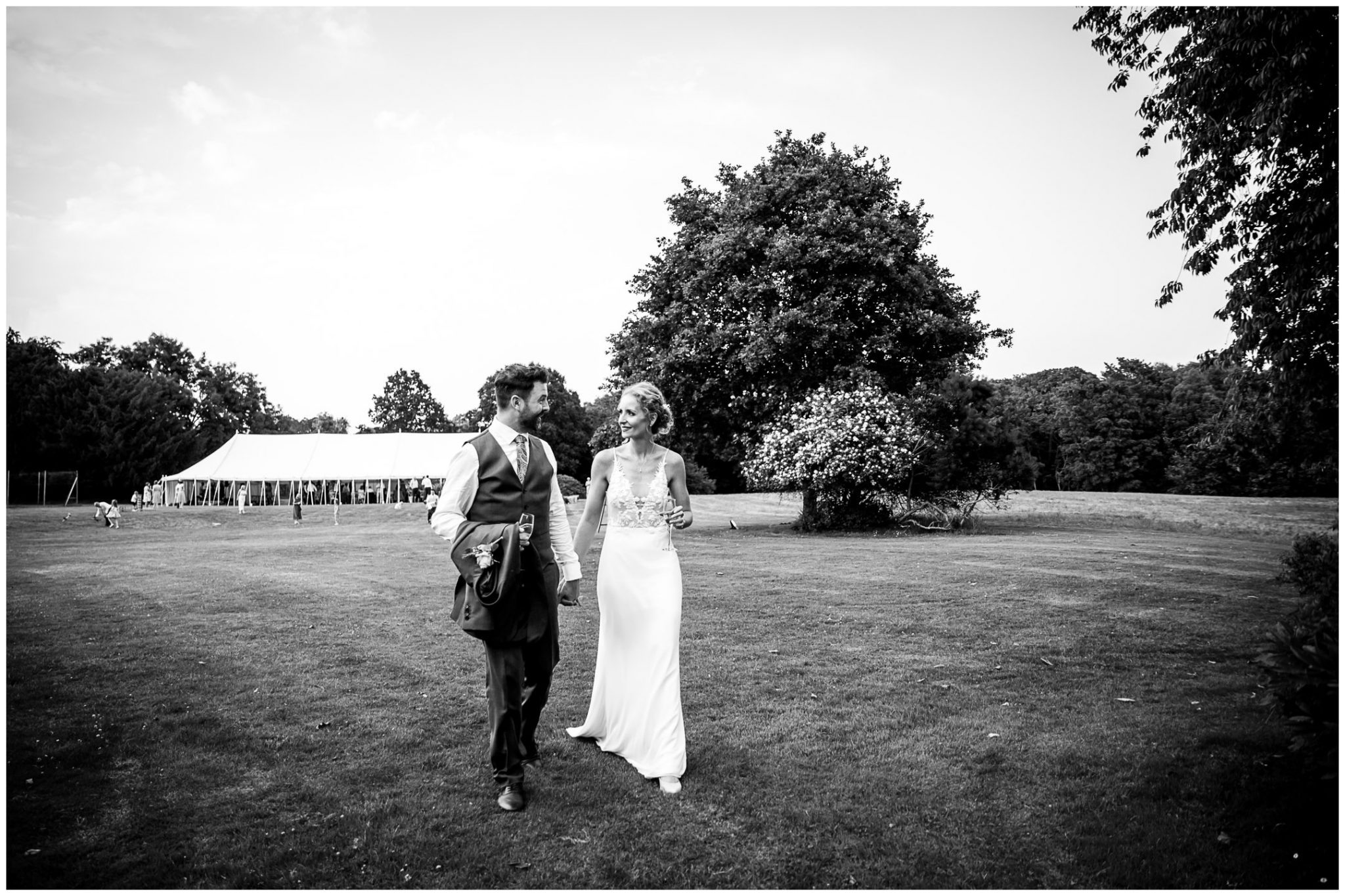 The couple walk away from the marquee towards the grounds and gardens of the house