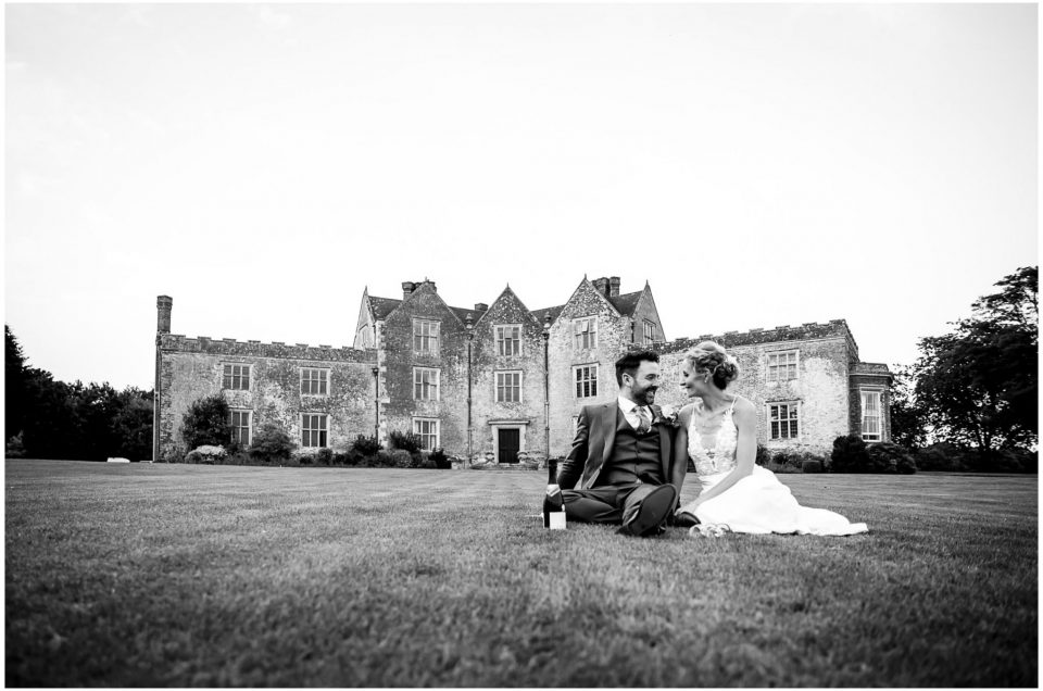 Black and white image of couple sat on the lawn in front of Newhouse Estate near Redlynch in the New Forest