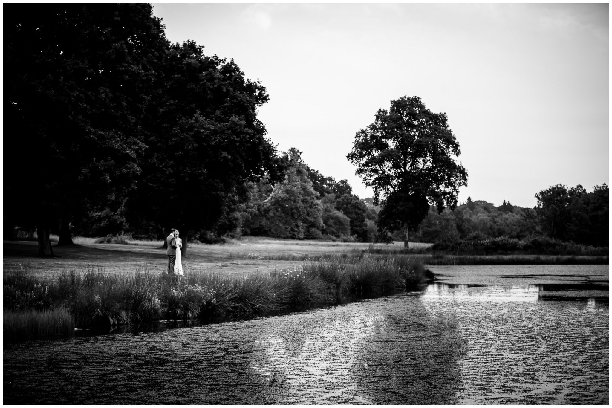 Bride and groom look out across the lake at the New House Estate Redlynch wedding venue