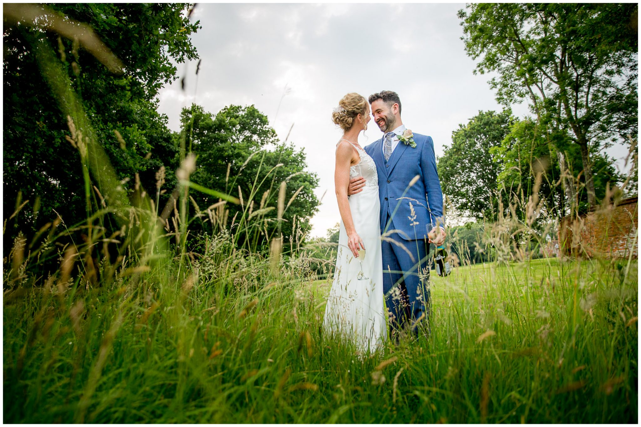 Couple portrait in long grasses at a Summer wedding in the New Forest