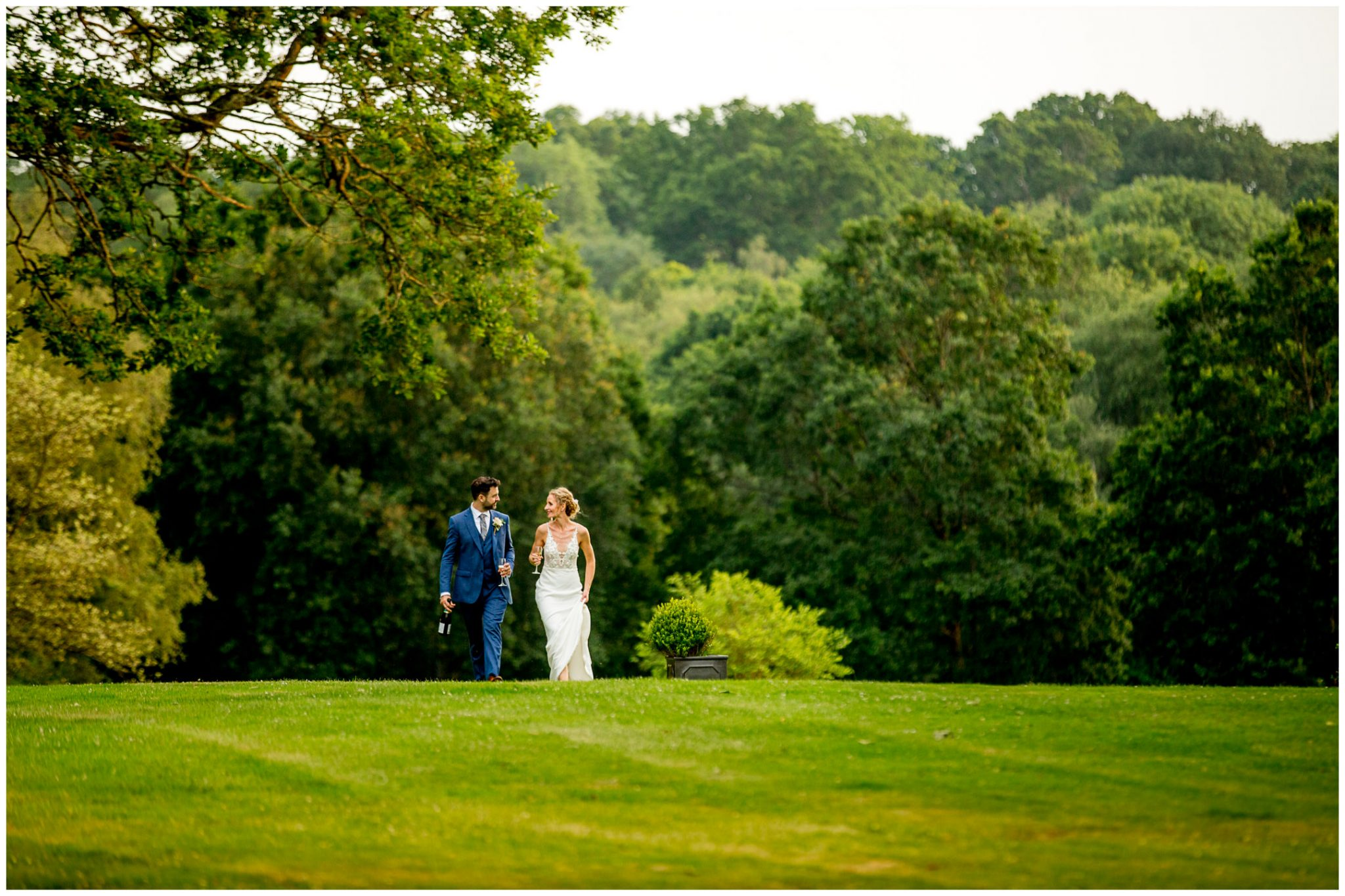 Bride and groom walk up the hill towards their wedding reception