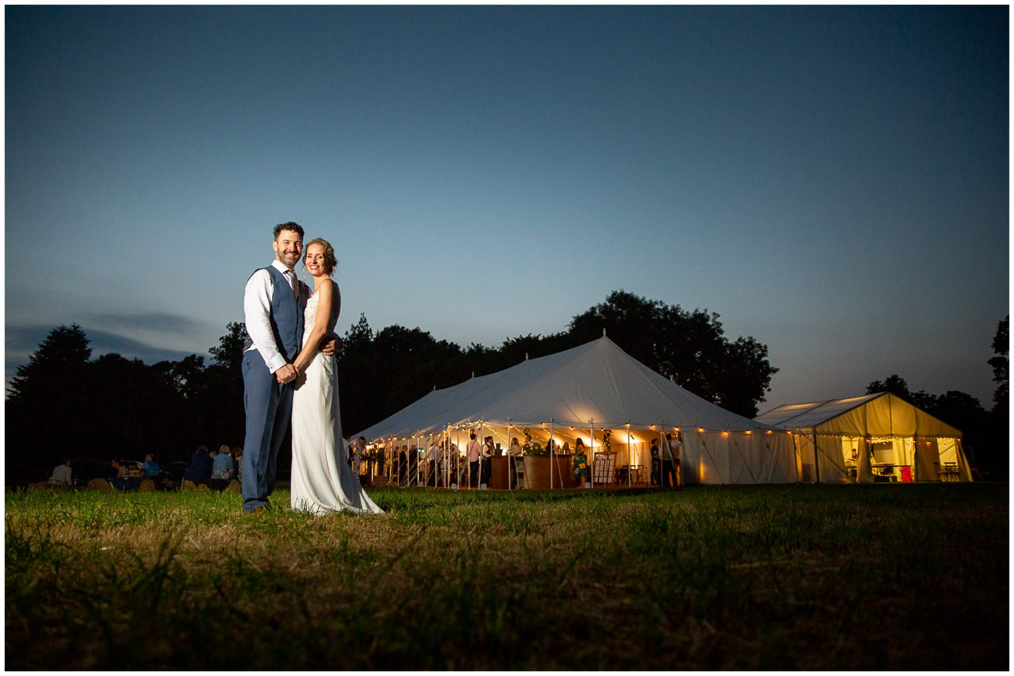 Couple portrait with wedding reception marquee lit up in the evening light