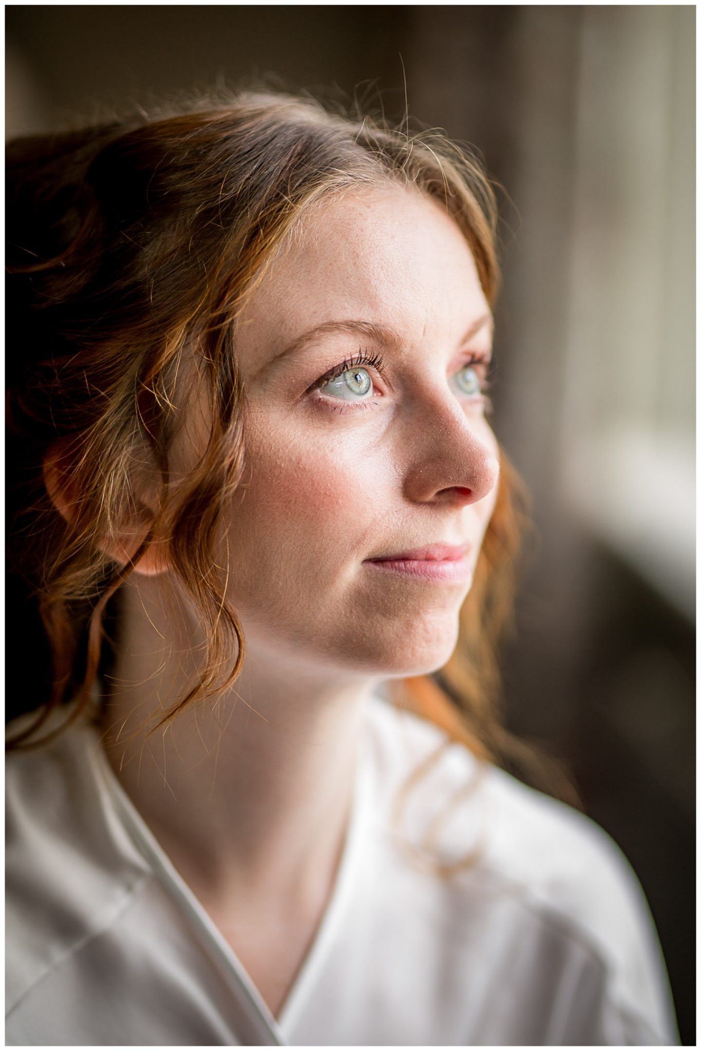 Bridal portrait during hair and makeup before the ceremony, using natural window light