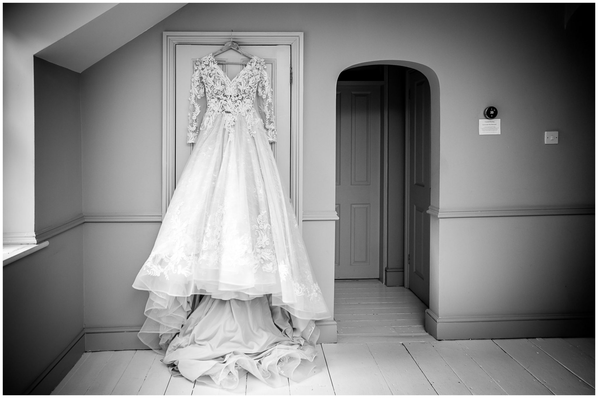 The wedding dress hangs on a door frame in the Gate House at Deans Court