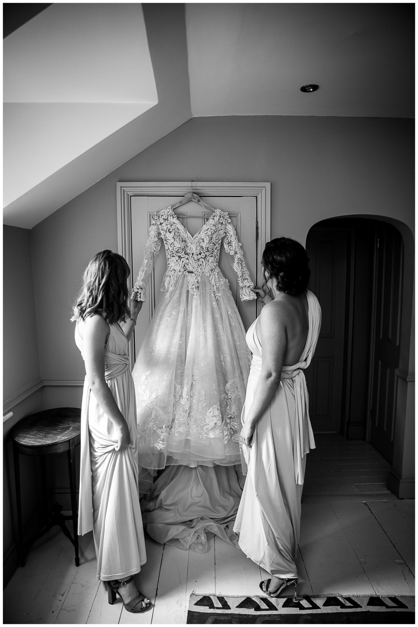 The bridesmaids look at the wedding dress