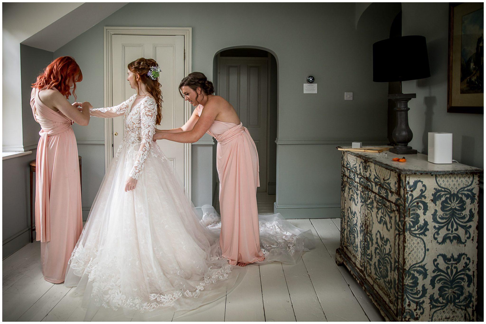 Bridesmaids help the bride get into the wedding dress
