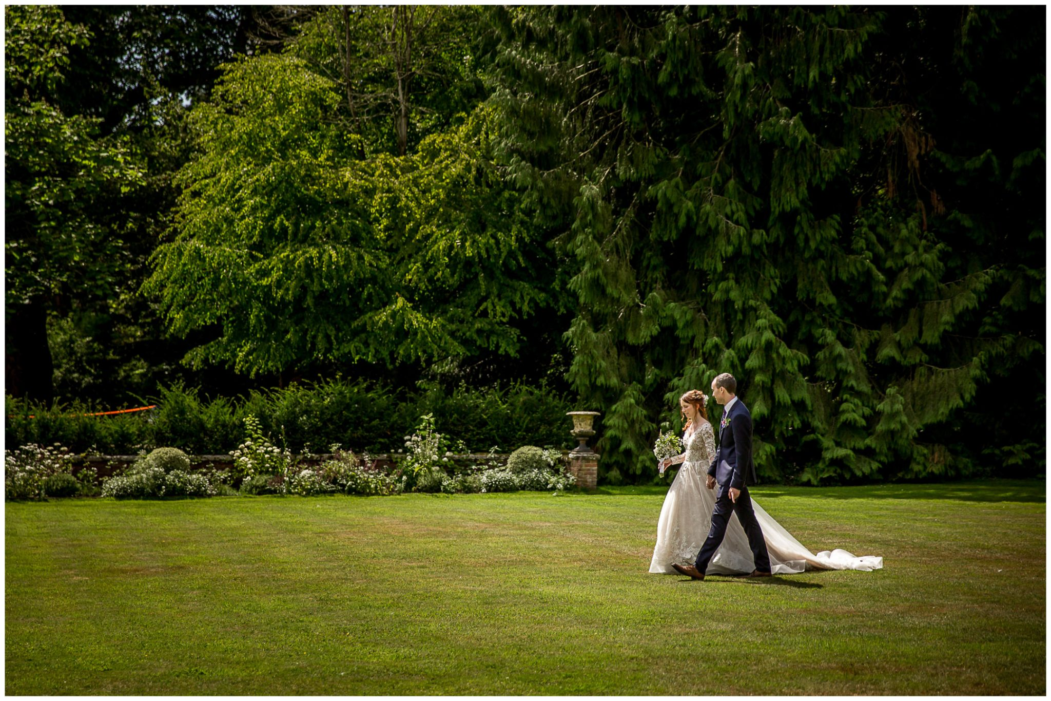 The couple walk across the lawn together towards their drinks reception