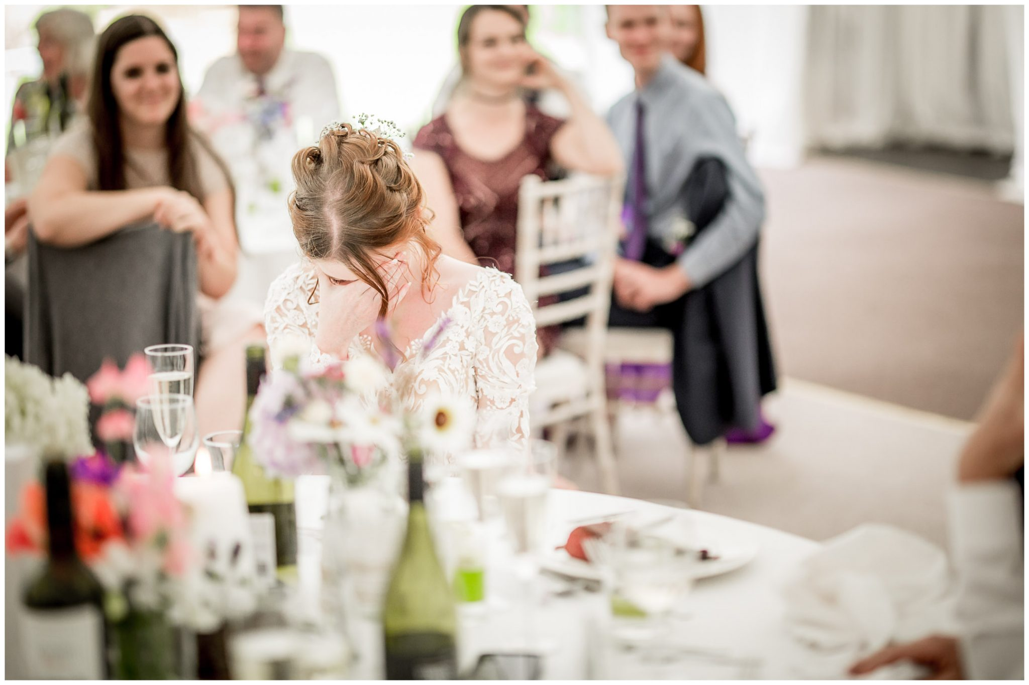 The bride reacts with embarrassment to one of the speeches