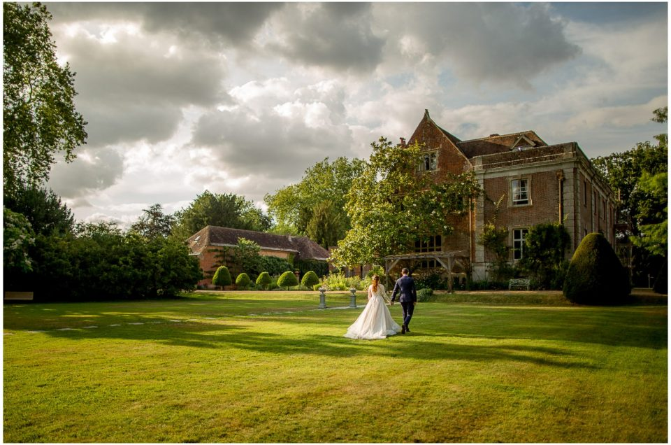 View of the back of the dress as bride and groom walk across the lawn towards the house
