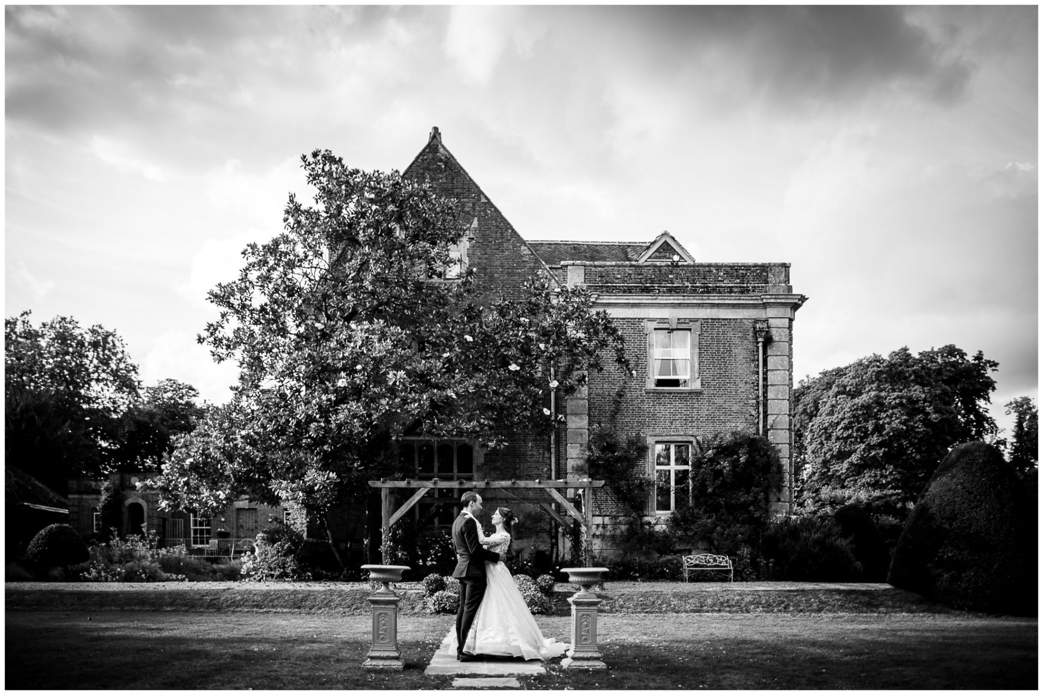 Black and white couple portrait in front of house and magnolia tree