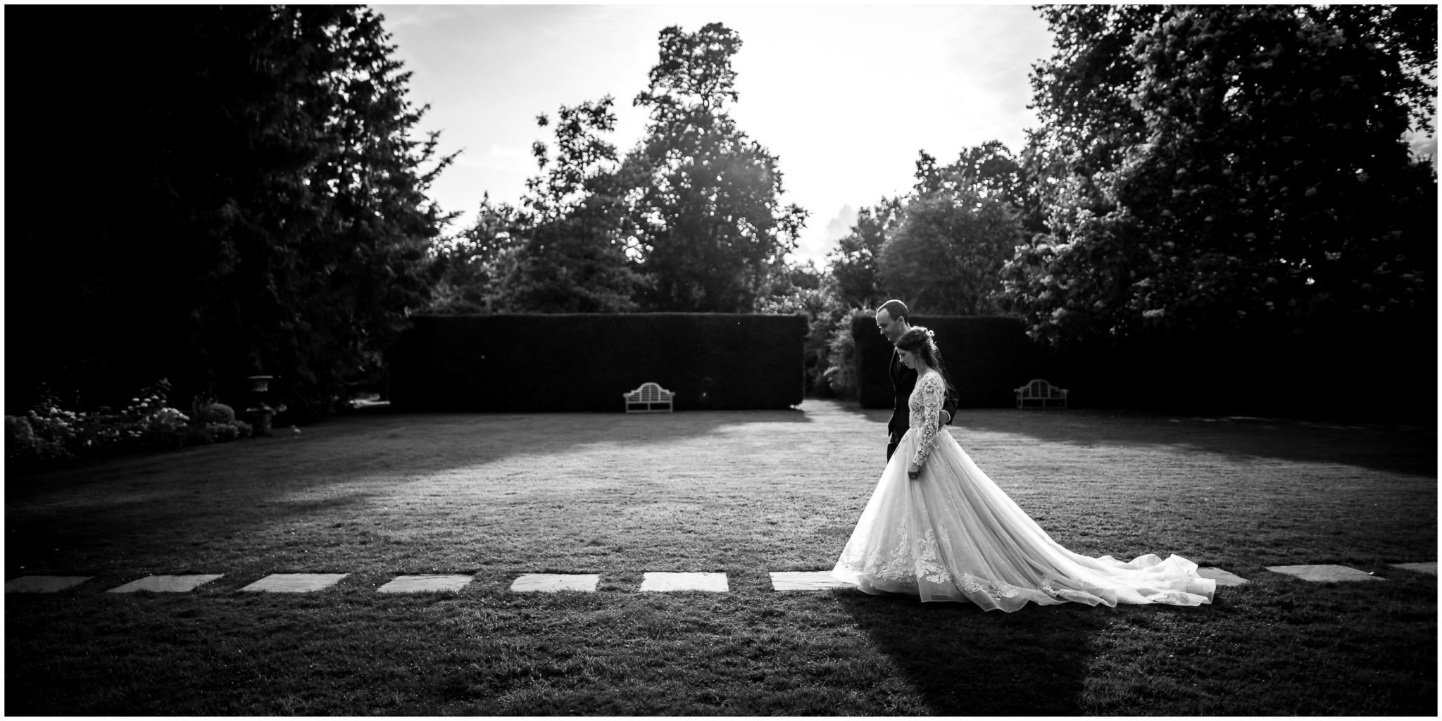 Black and white photo of bride and groom crossing the lawn on the way back to the party