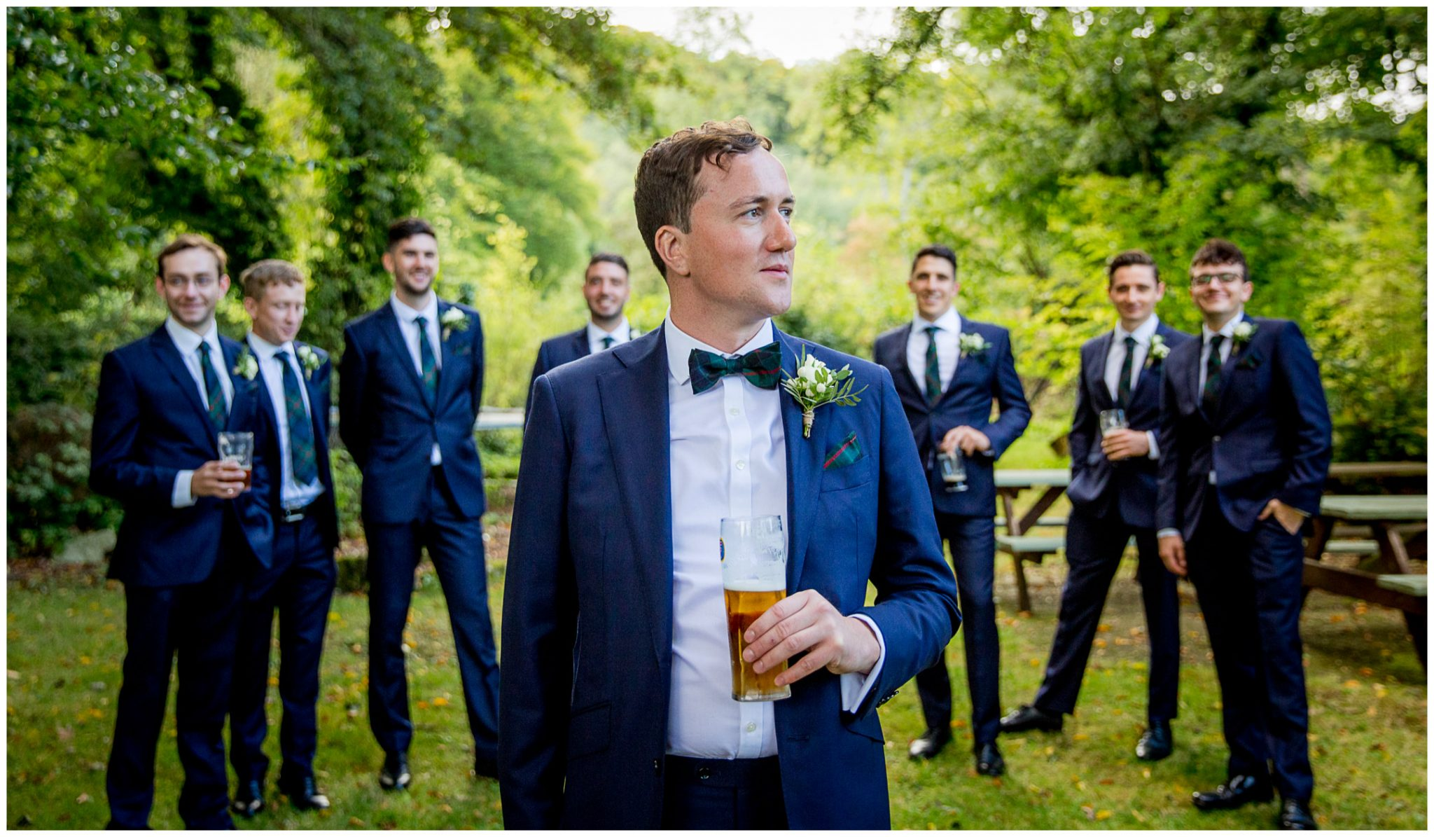 Groom portrait with groomsmen in background