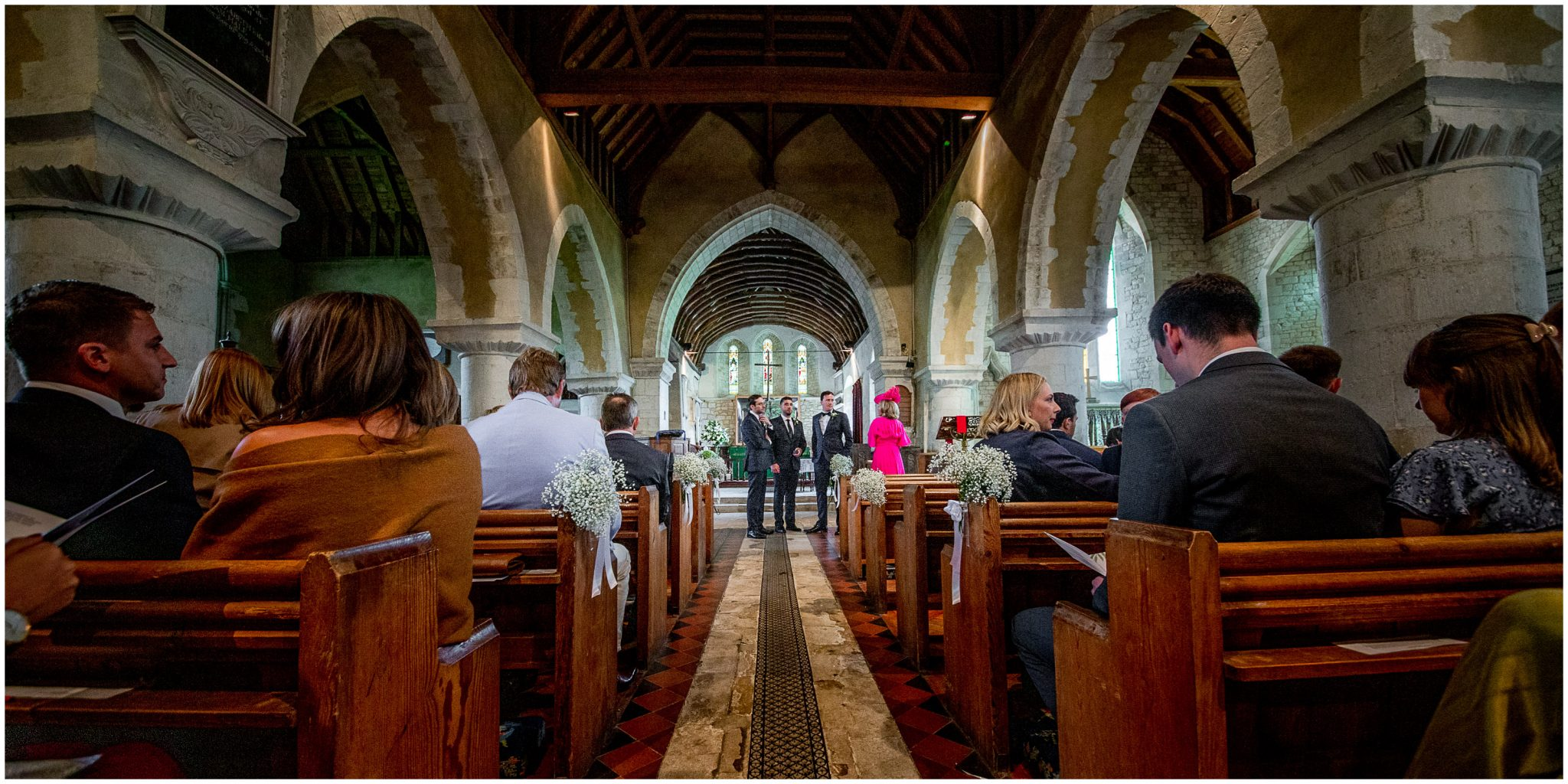 Wide view of church from the rear down the aisle to where groom and best men are standing