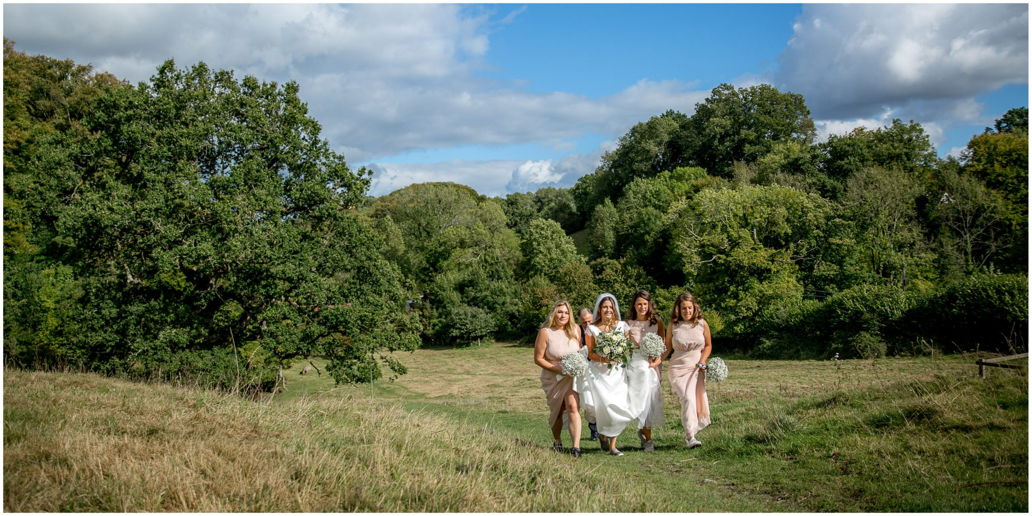 Bride and bridesmaids walking up the hill towards the church