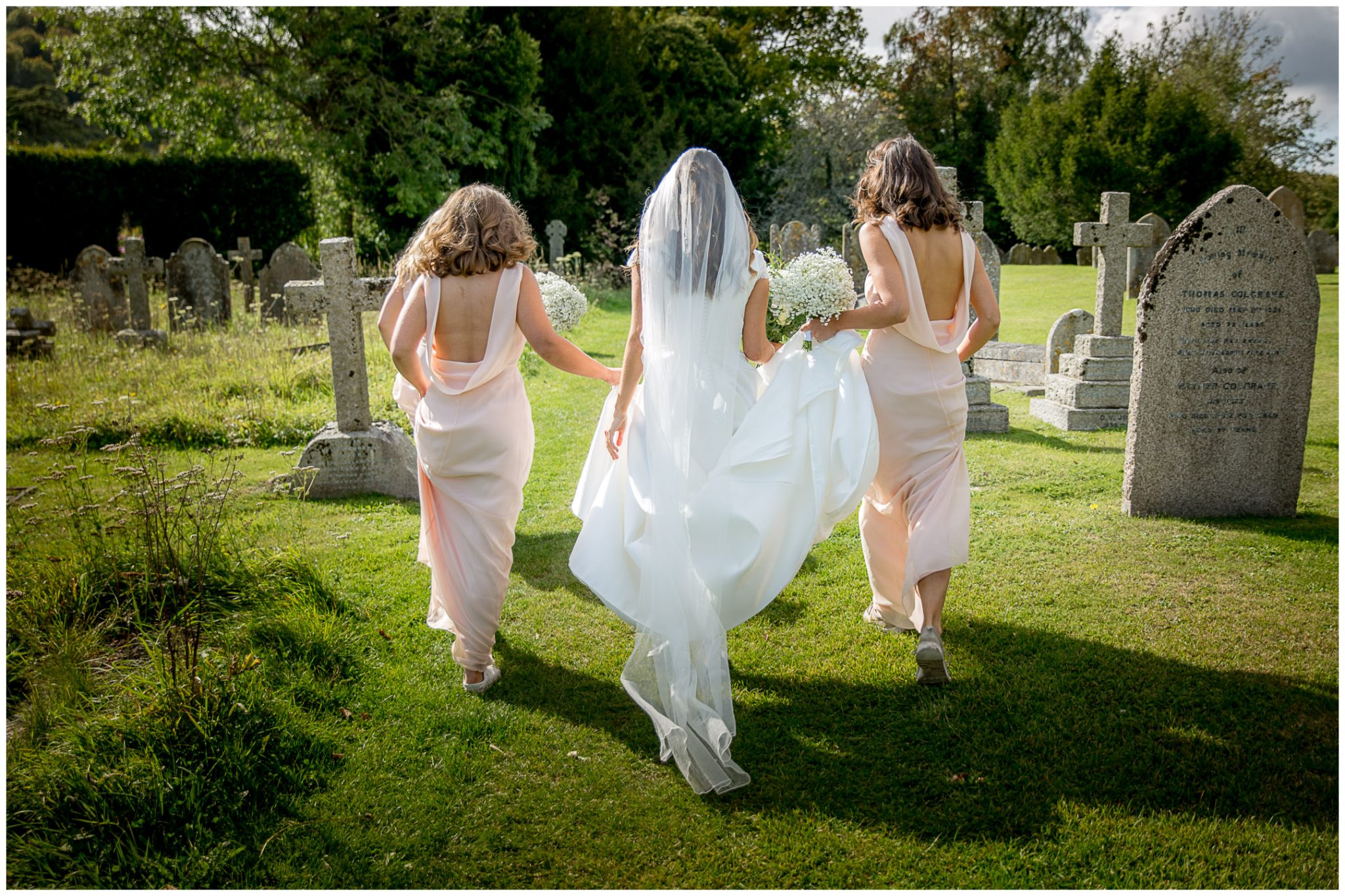 The back of the dress and the bride walks through the churchyard in the sunshine