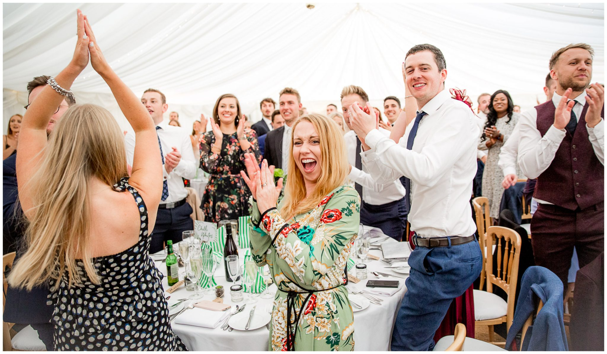 Wedding guests cheer as the couple make their entrance to the marquee