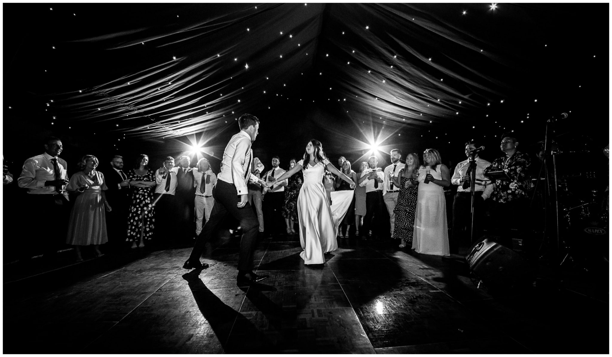 Wedding guests surround the couple for their first dance