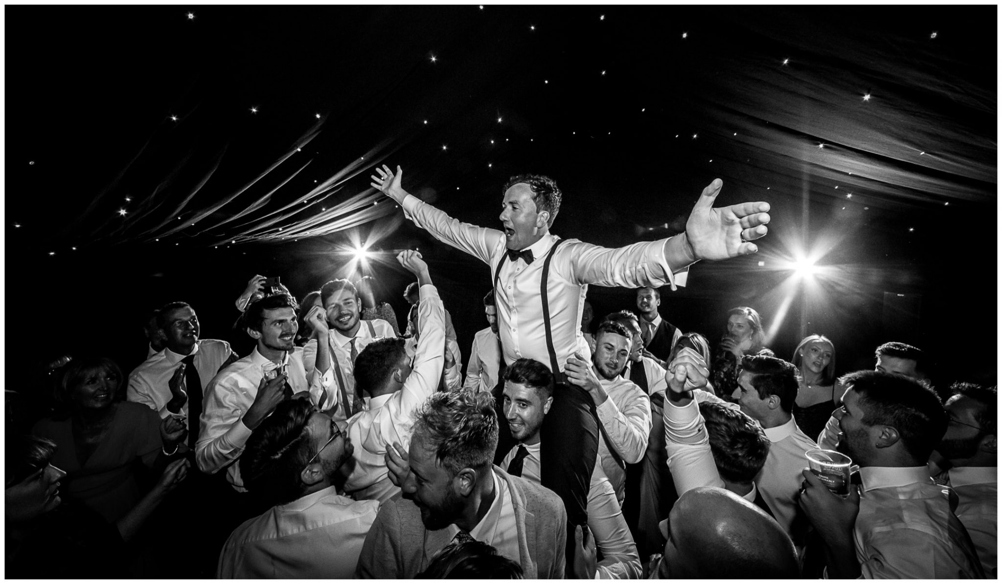 The groom is lifted onto his friends' shoulders during the evening party
