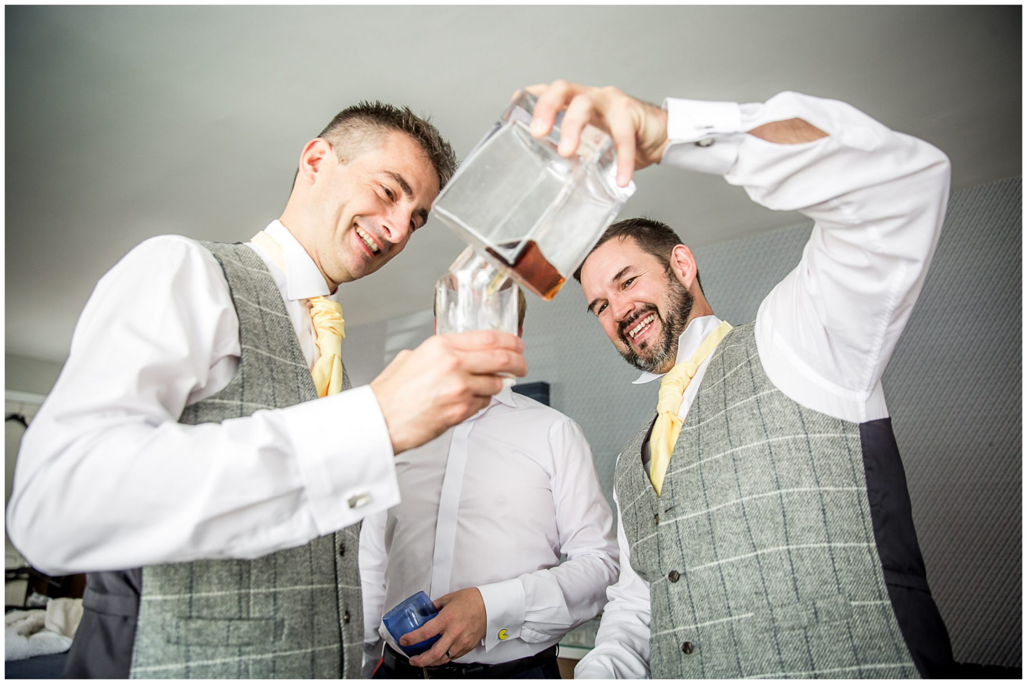 The groom pours a drink for his groomsmen