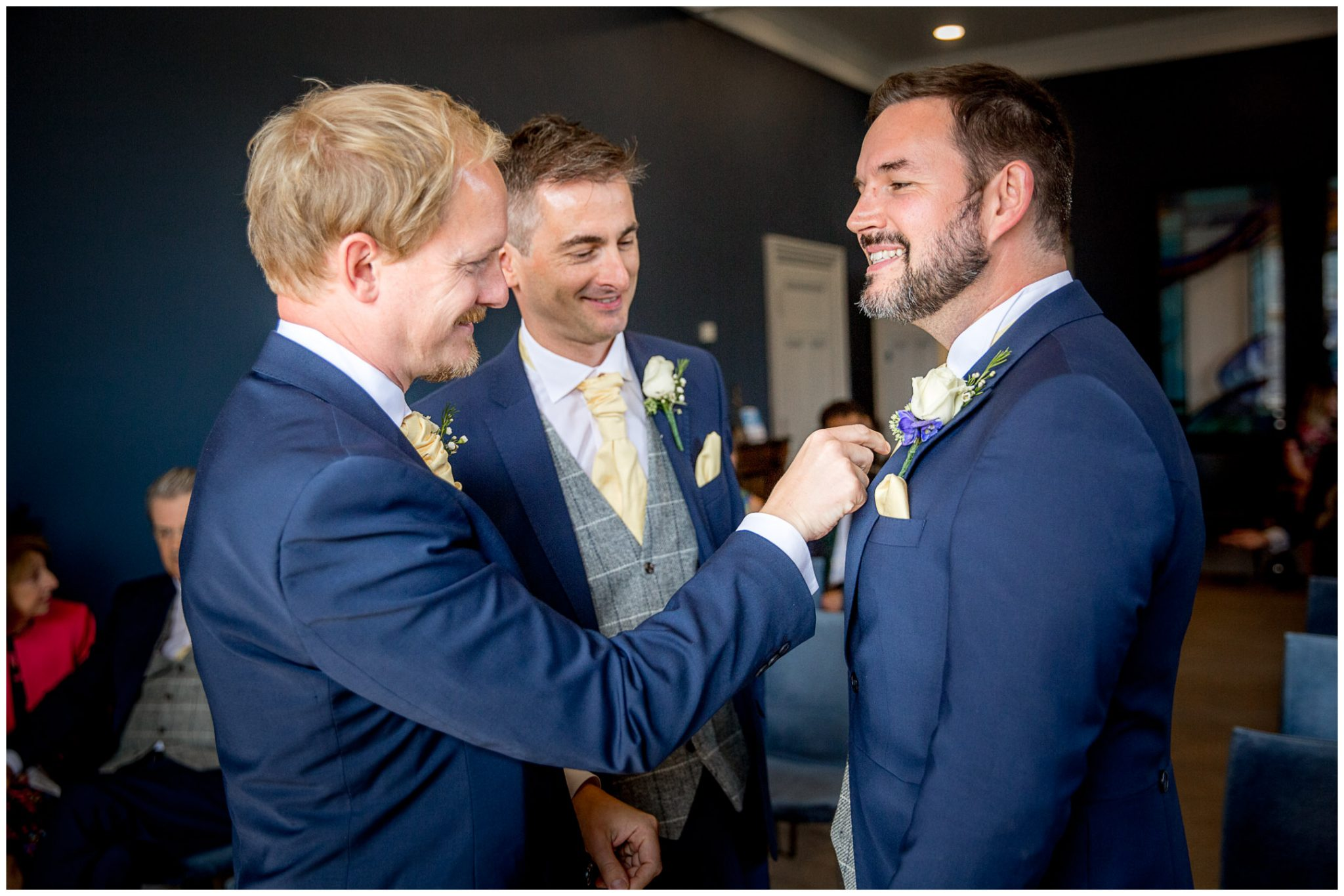 Groomsmen make final adjustments to the groom's tie before the ceremony