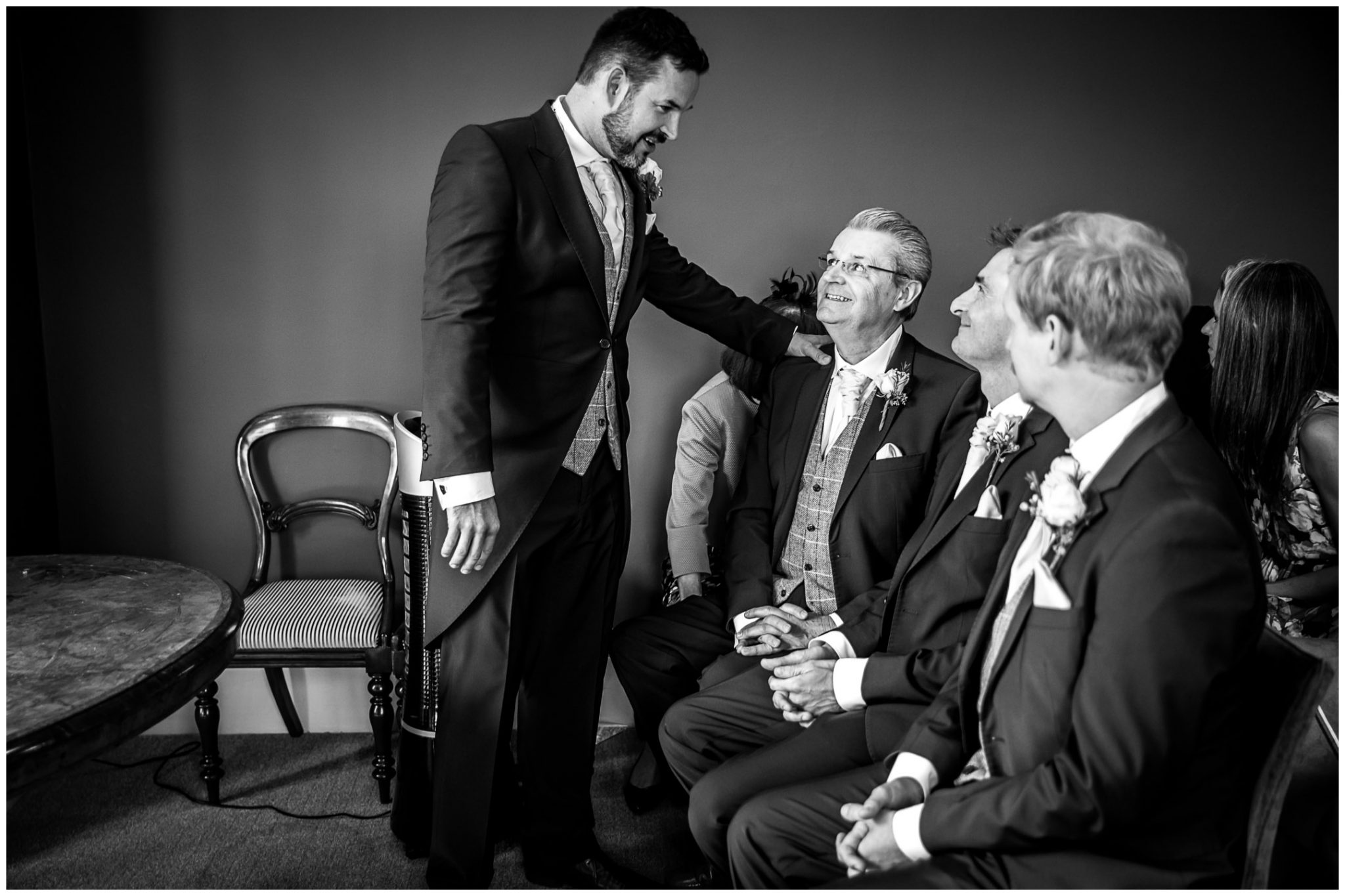 The groom chats with his father in the Castle Room at Winchester registry office