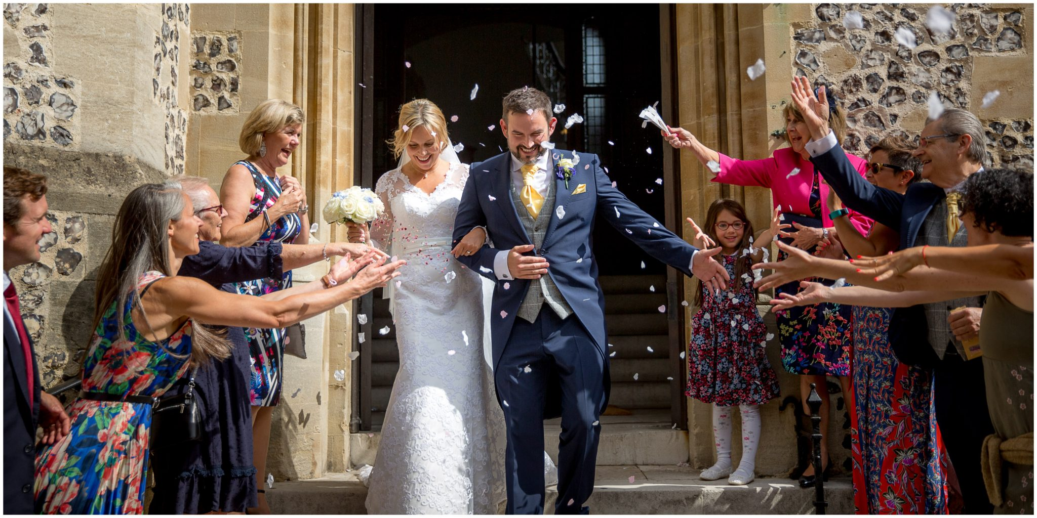 The bride and groom emerge from the registry office to be showered with confetti