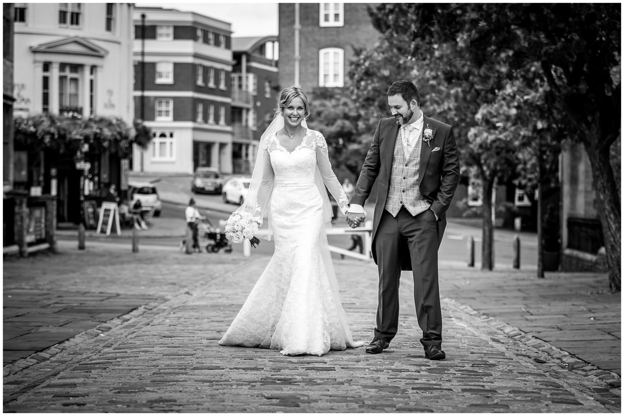 The bride and groom walk together along Castle Avenue in Winchester