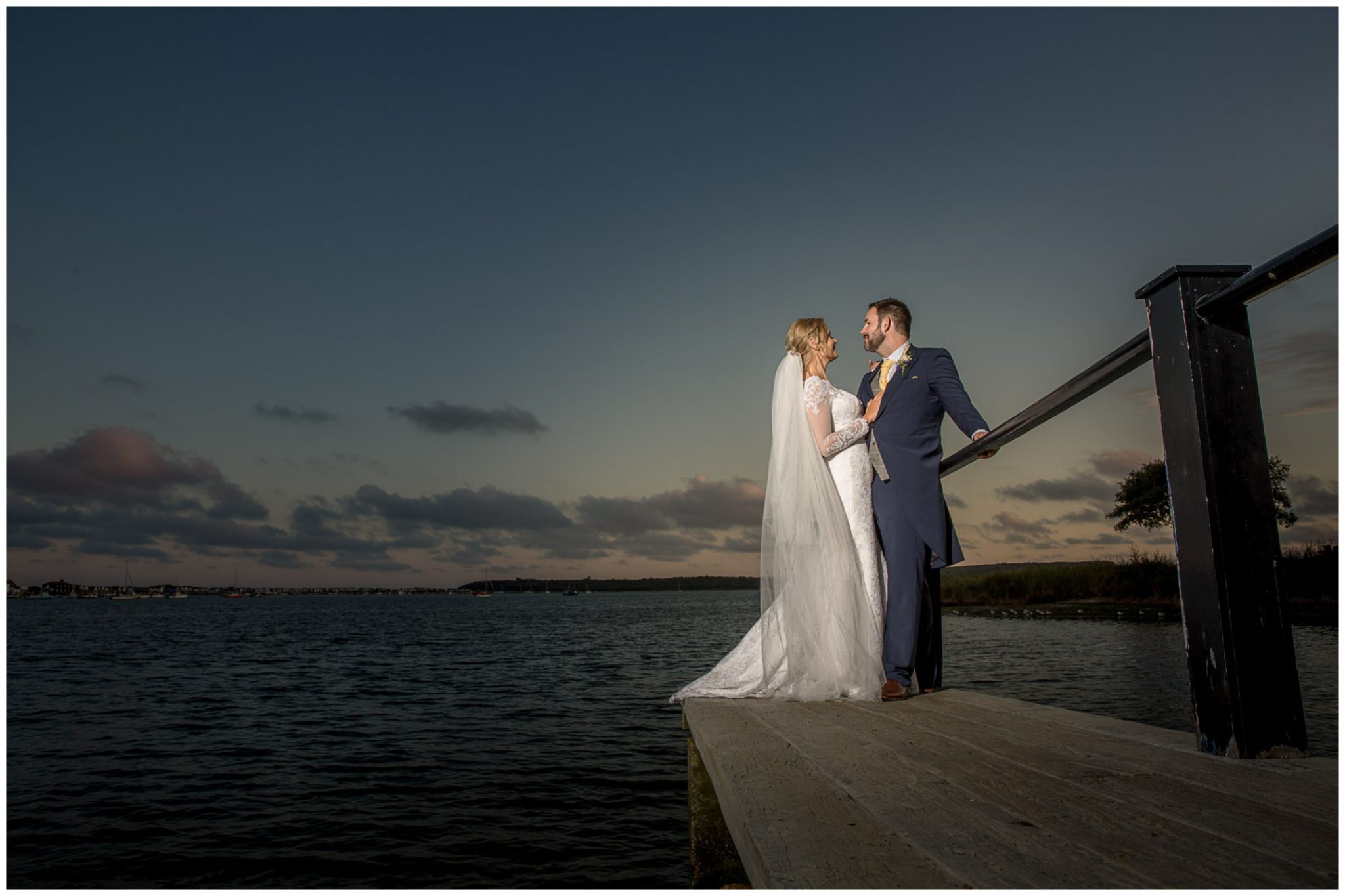 Couple stood on the jetty by the water in the evning light