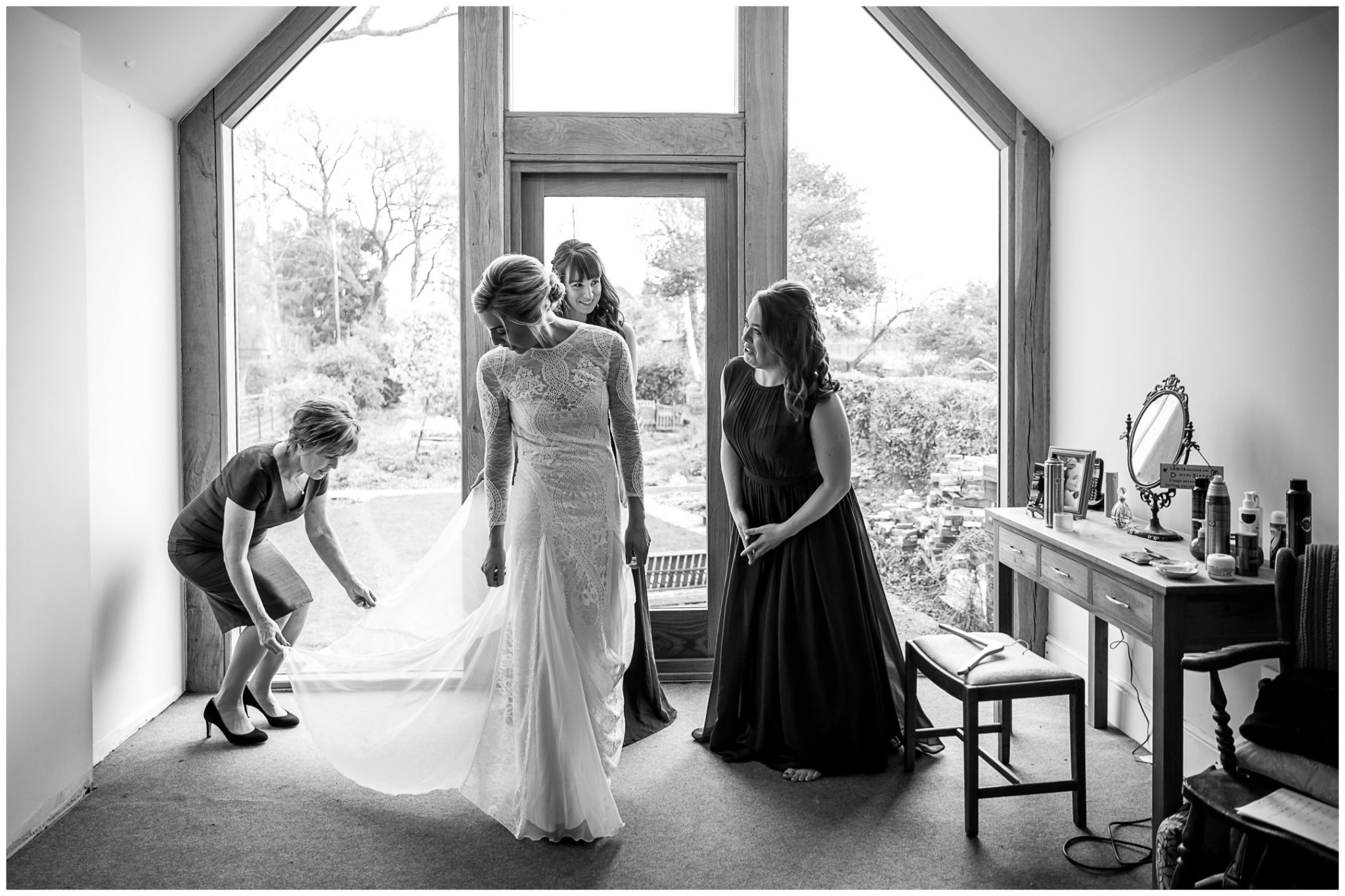 The bride's mother and her bridesmaids help her to get into her wedding dress