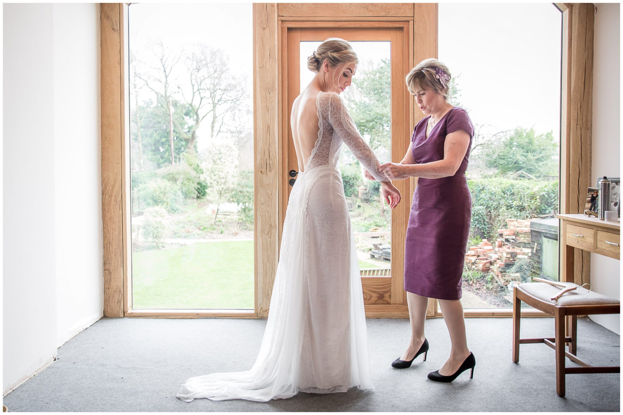 The bride's mother helps her to get dressed