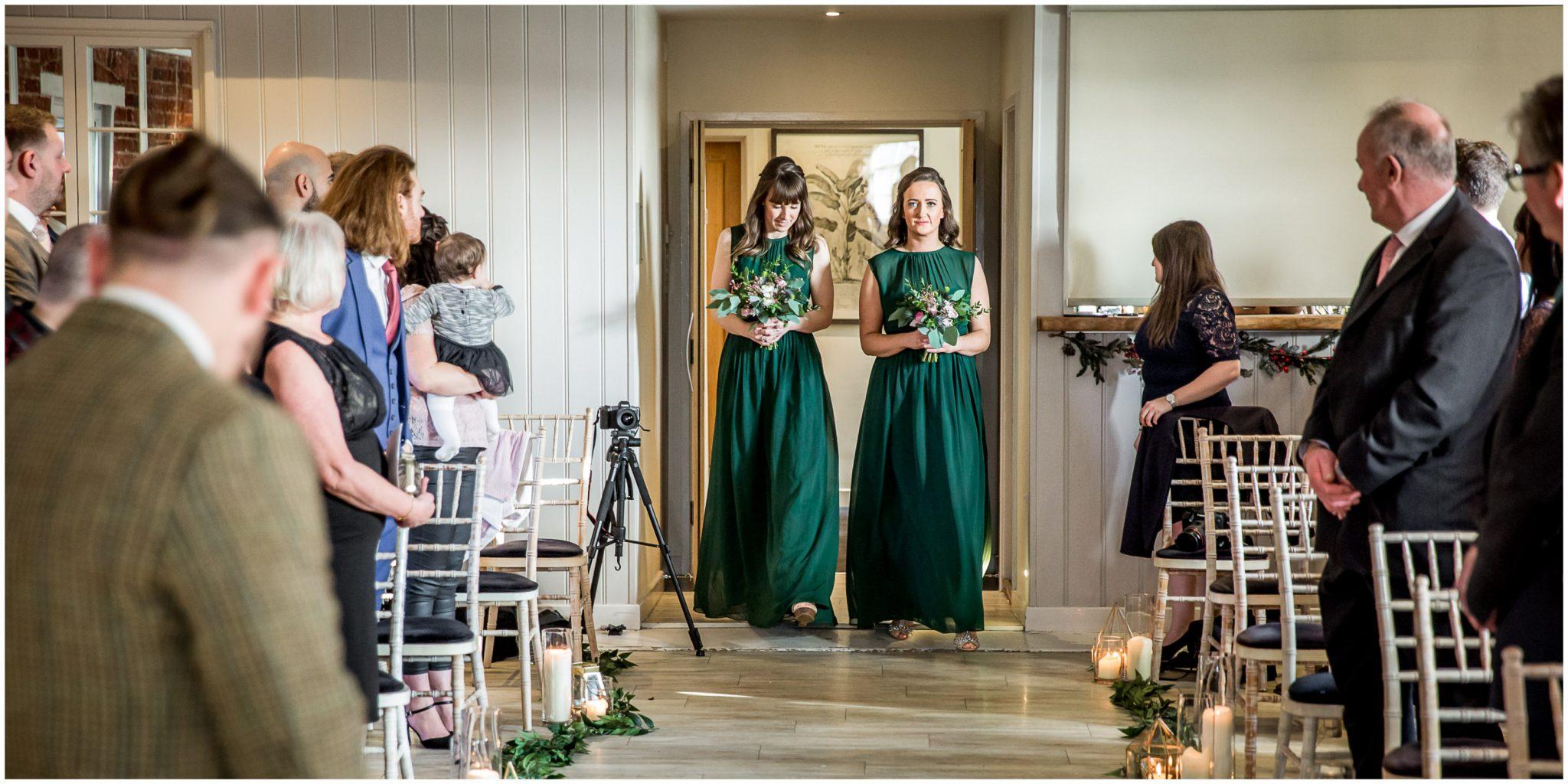 Bridesmaids enter the ceremony room ahead of the bride