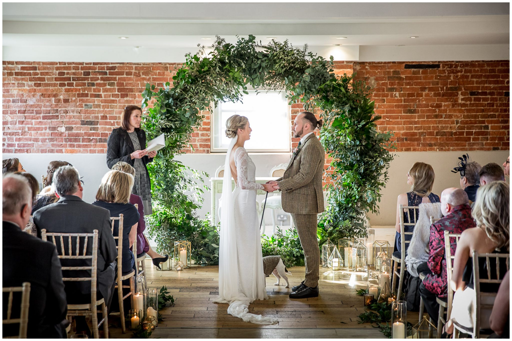 The couple turn to face each other in front of a magnificent floral moon gate feature