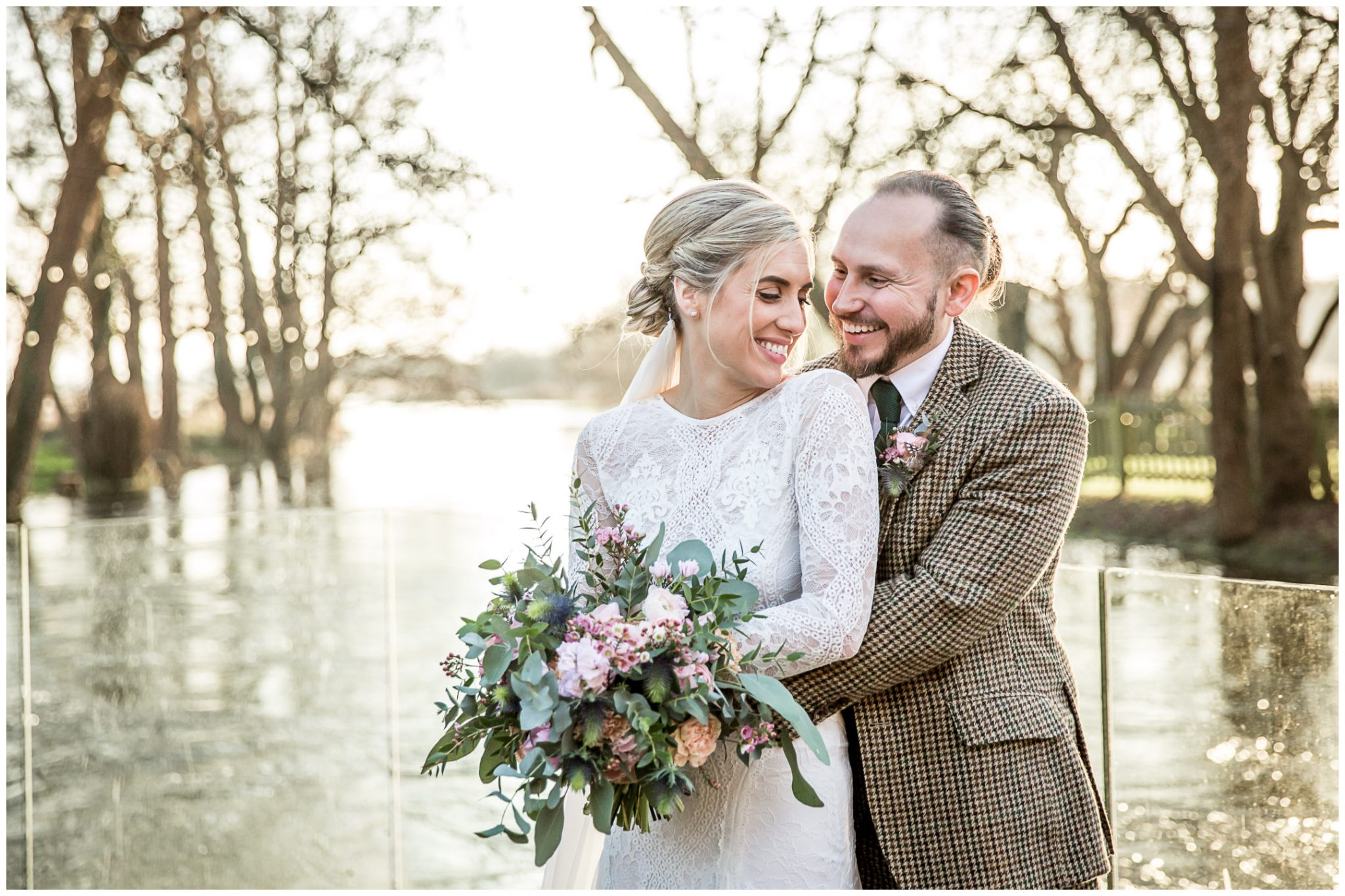Bride and groom portrait in Winter light by the river at Sopley Mill
