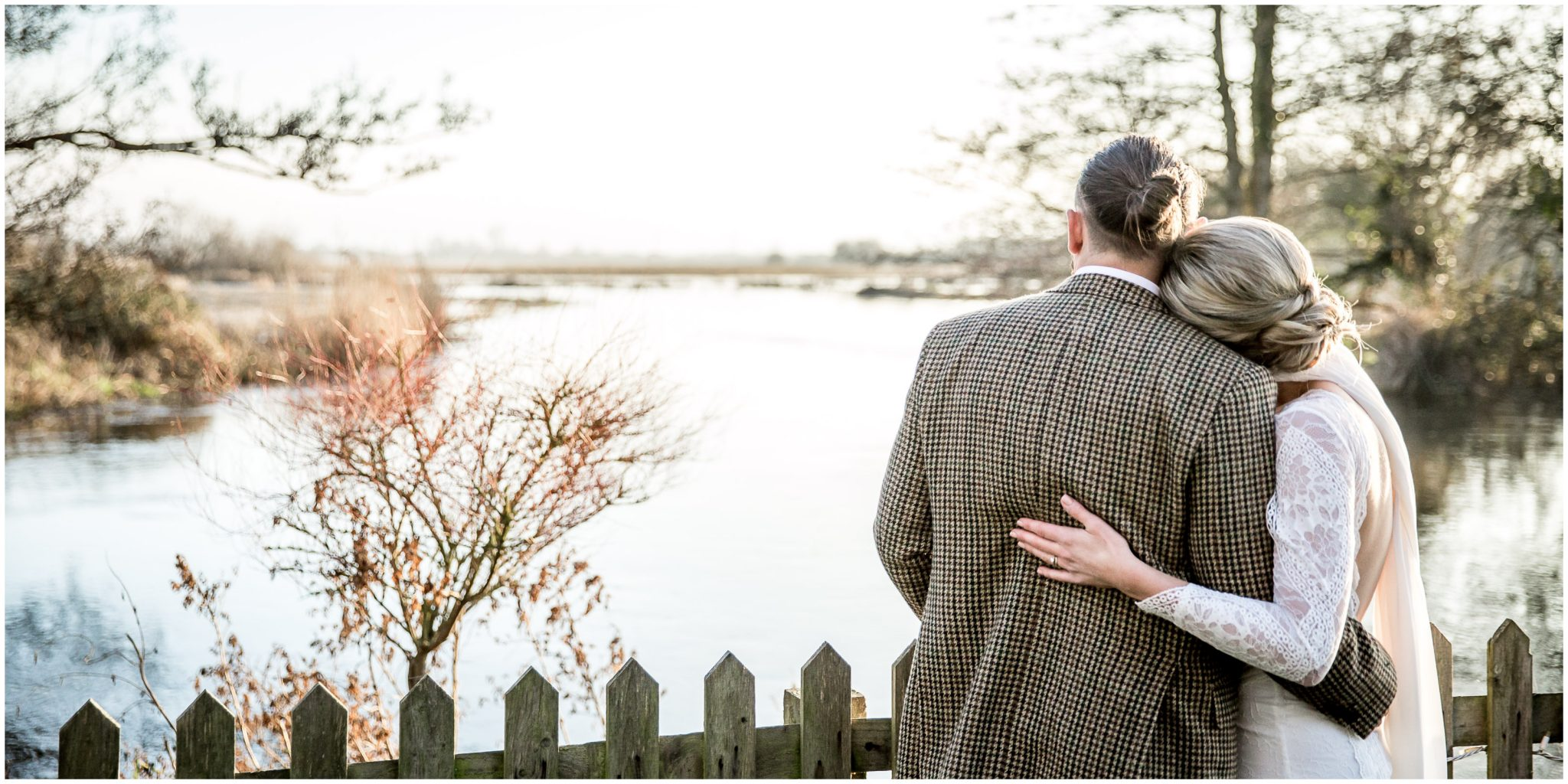 Bride and groom looking down the river at the end of the gardens at Sopley Mill