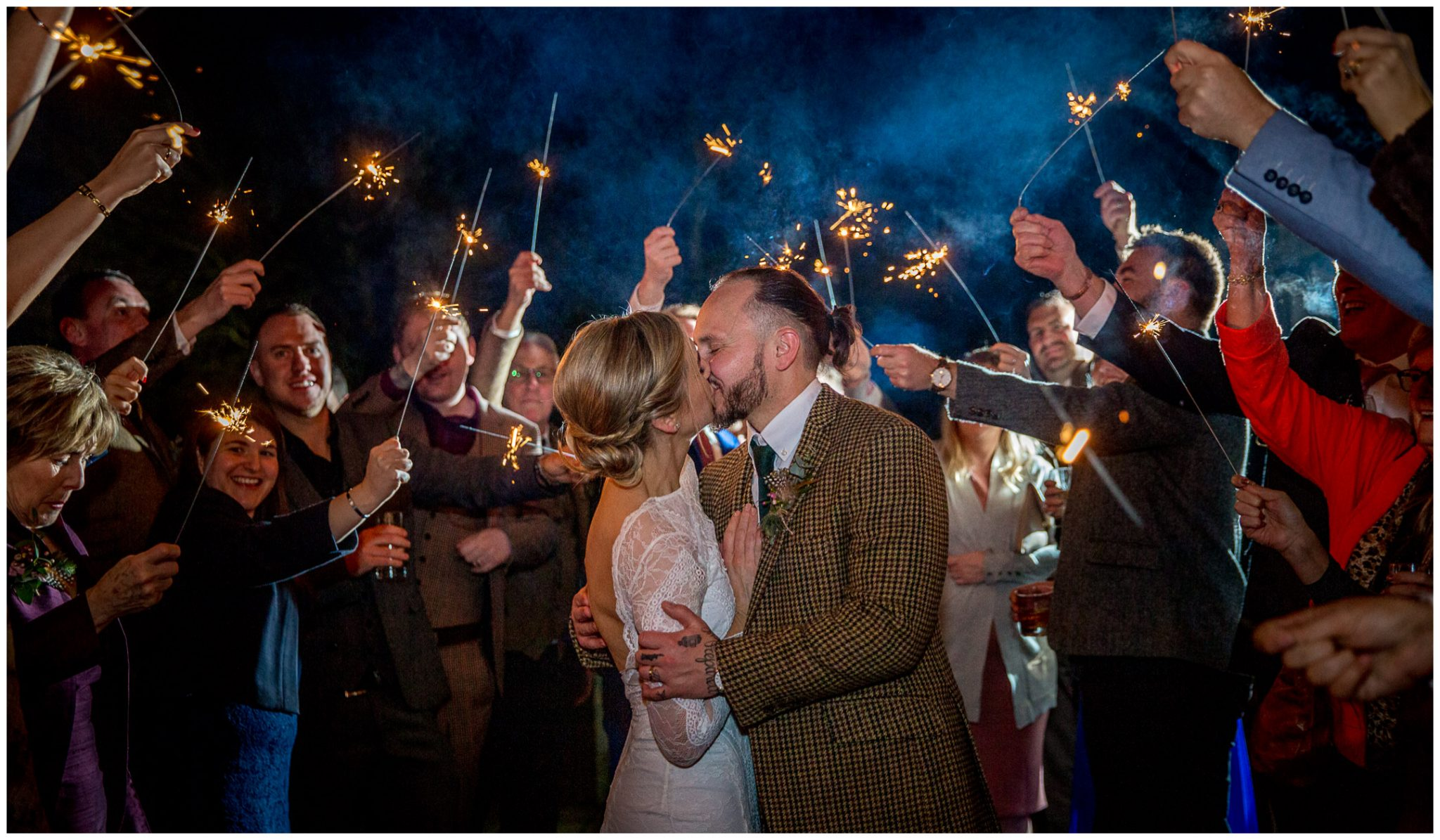 The couple kiss during a sparkler photo