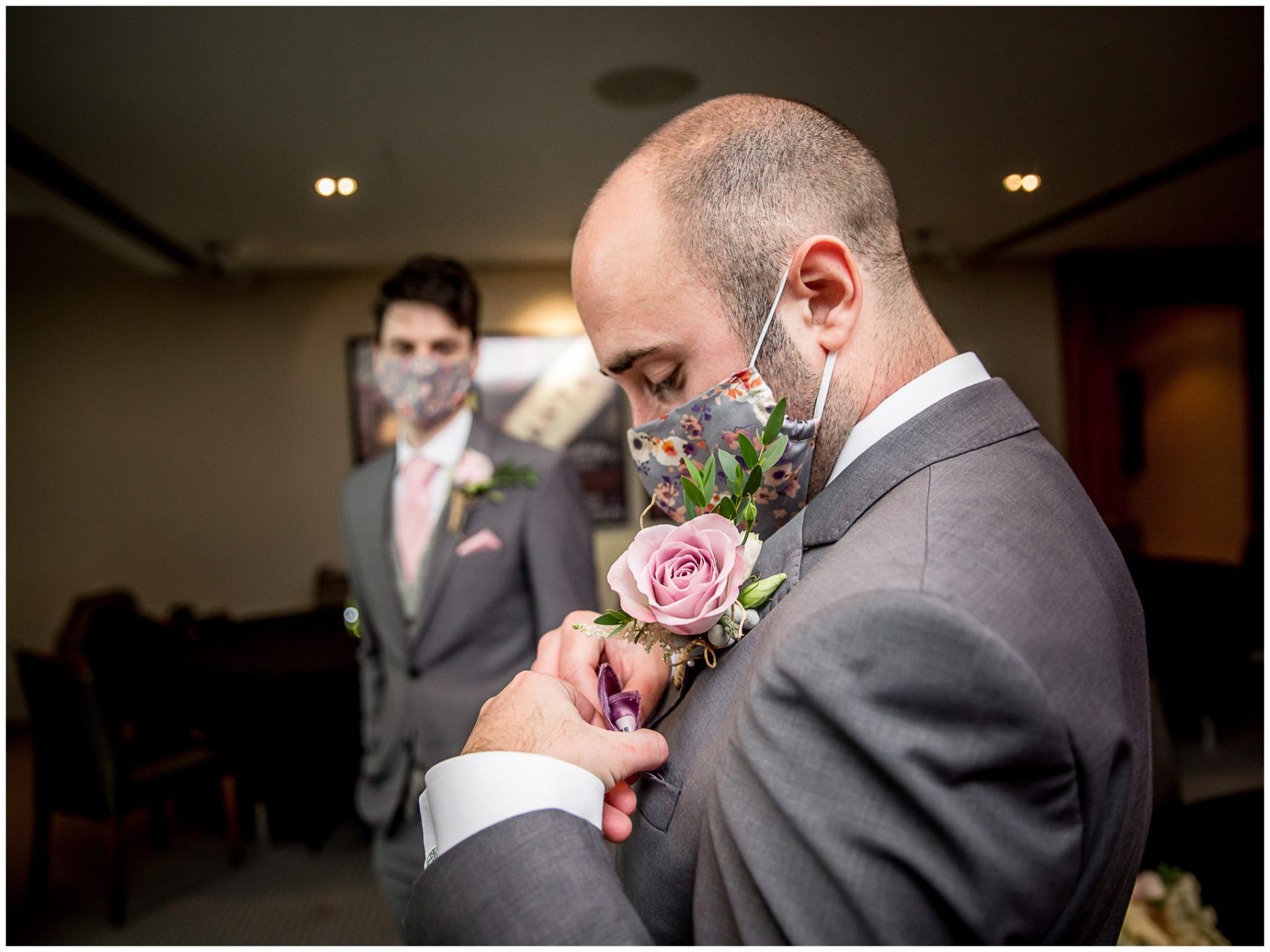 Groom getting ready and putting flower in button hole, wearing mask