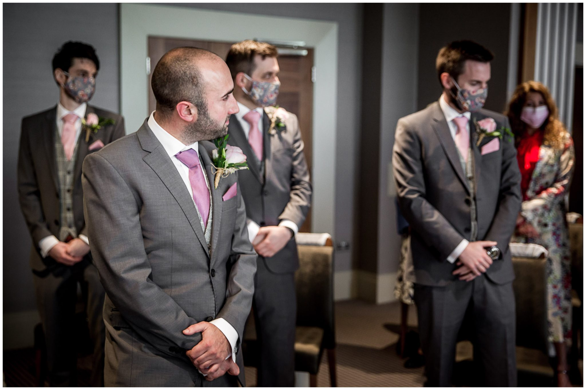 The groom turns and looks as the bride walks down the aisle