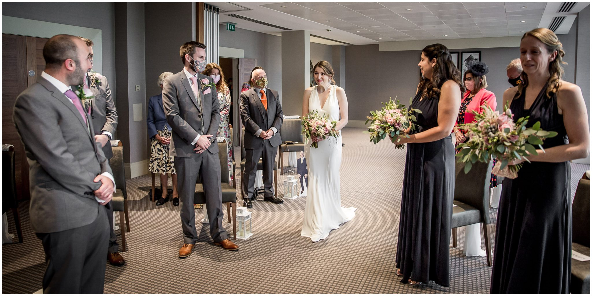 The bride walks down the aisle as wedding guests watch