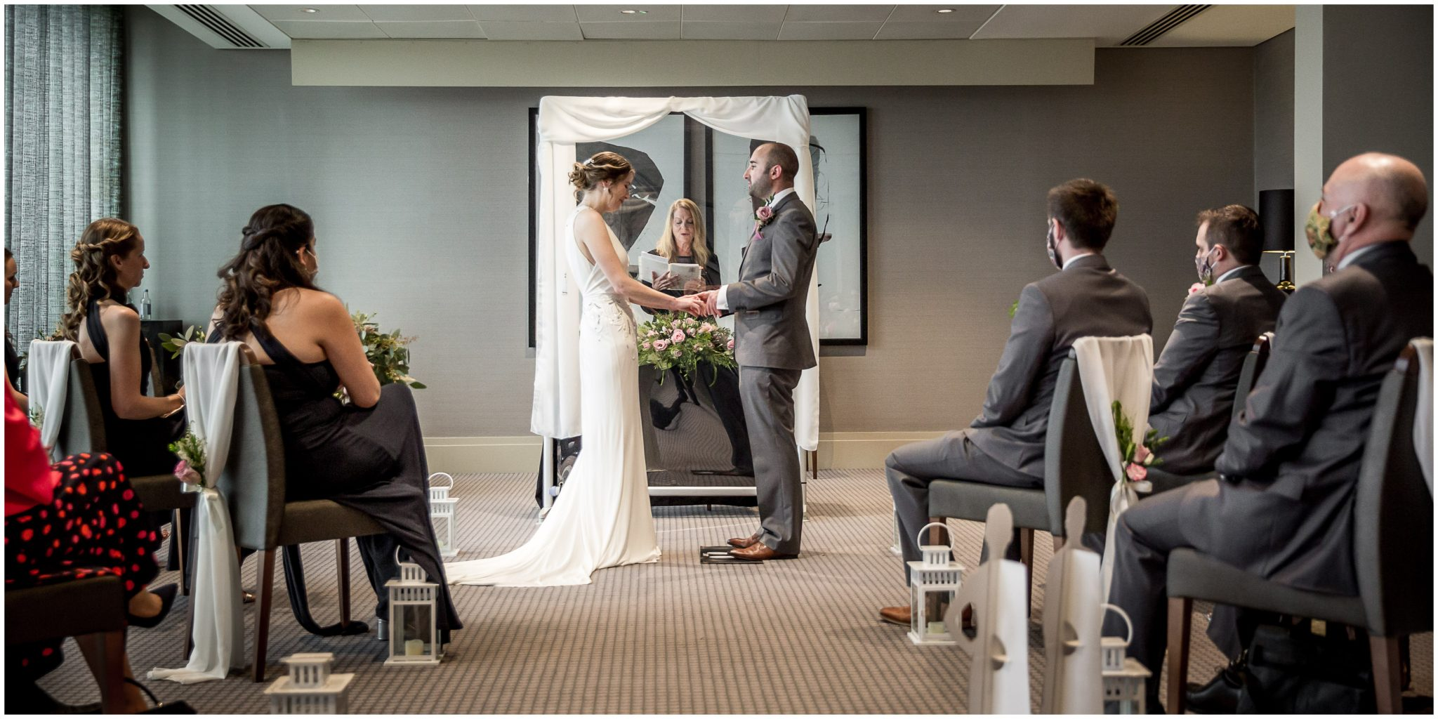 Couple holding hands as registrar reads marriage vows