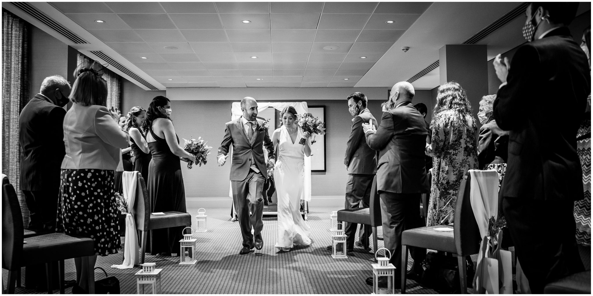 Black and white photo of couple walking down the aisle together