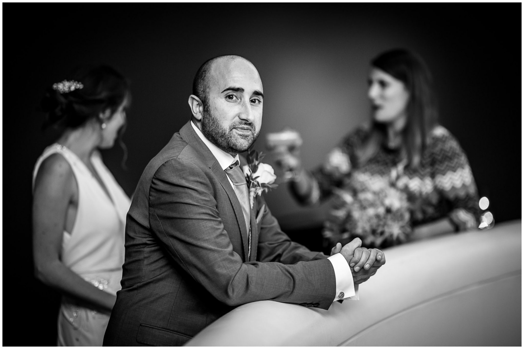 Black and white portrait of groom during drinks reception